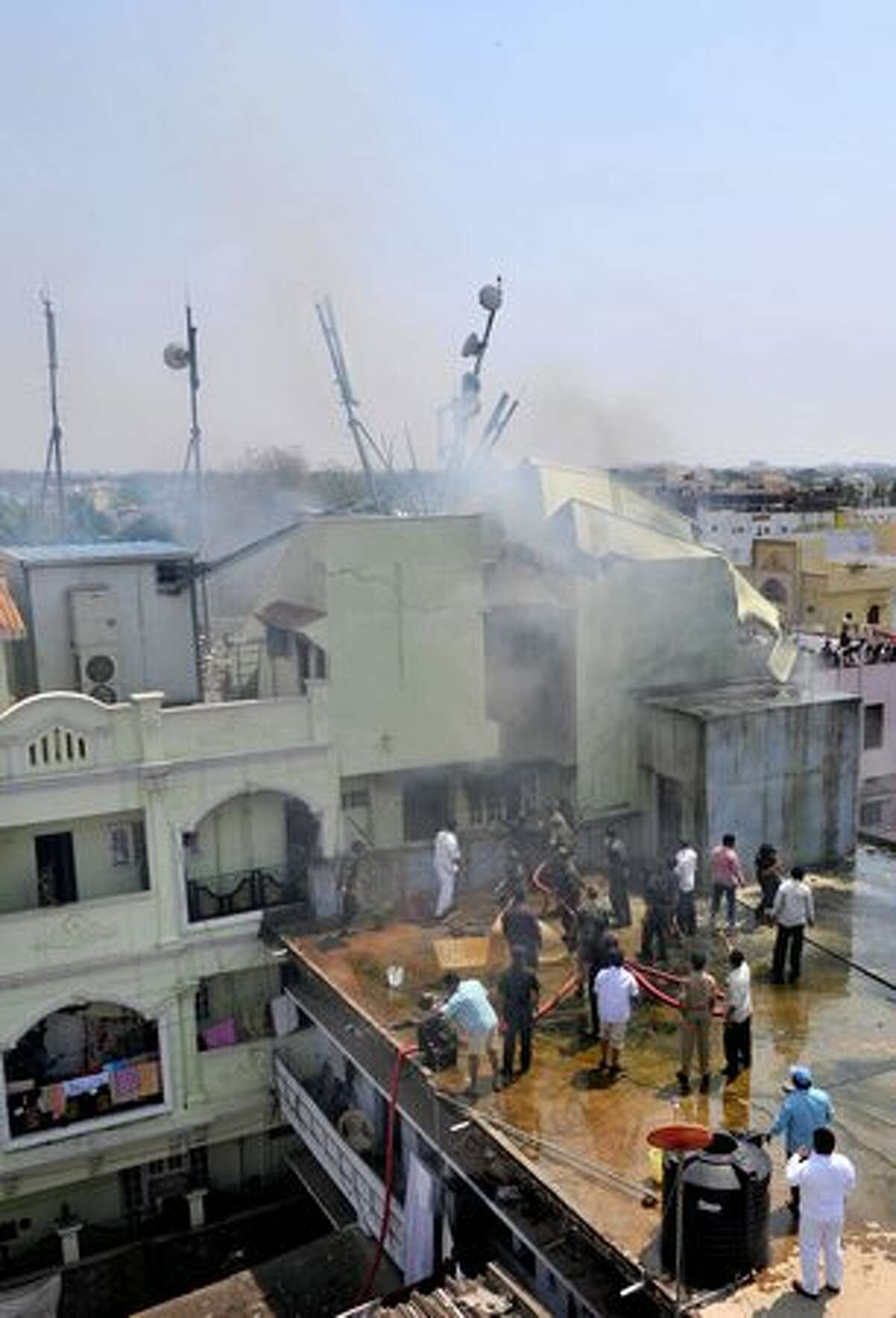 Indian residents and rescue personnel attempt to douse a fire in a building after an aircraft of The Indian Naval Aerobatic Team 'Surya Kiran' crashed during the India Aviation 2010 show at Begumpet Airport in Hyderabad on March 3, 2010. A navy aircraft taking part in an acrobatics show on the first day of an air show in the southern Indian city. The plane, a two-seater Kiran MK-II built by the state-run Hindustan Aeronautics, was part of a four-plane formation when it crashed. The accident occurred on the opening day of the India Aviation 2010 show, a five-day civil aviation exhibition.