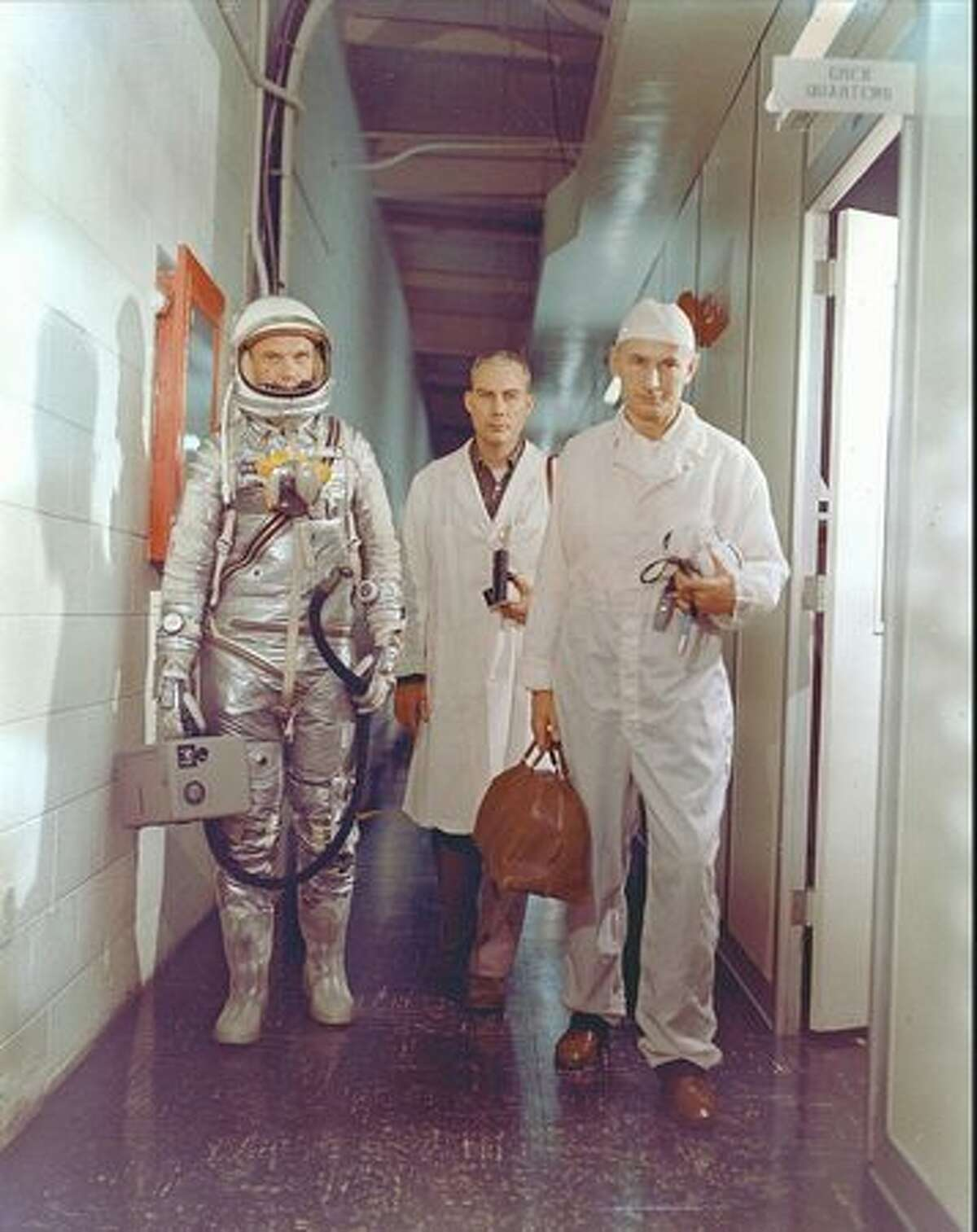 Astronaut John Glenn, NASA flight surgeon William Douglas and equipment specialist Joseph W. Schmidt leave crew quarters prior to the Mercury-Atlas 6 mission launch on Feb. 20, 1962. Glenn is in his pressure suit and is carrying the portable ventilation unit.