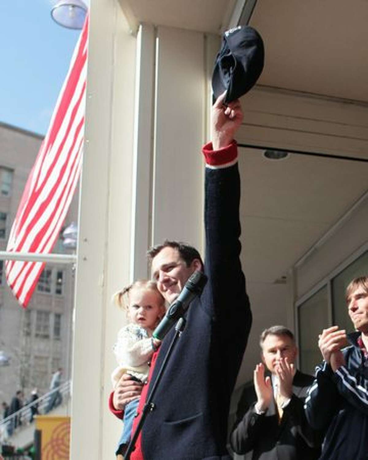 Luger Christian Niccum waves to the crowd as he holds his daughter Hayden Lulu Niccum as local Olympians are welcomed home after competing in the Vancouver Olympics.