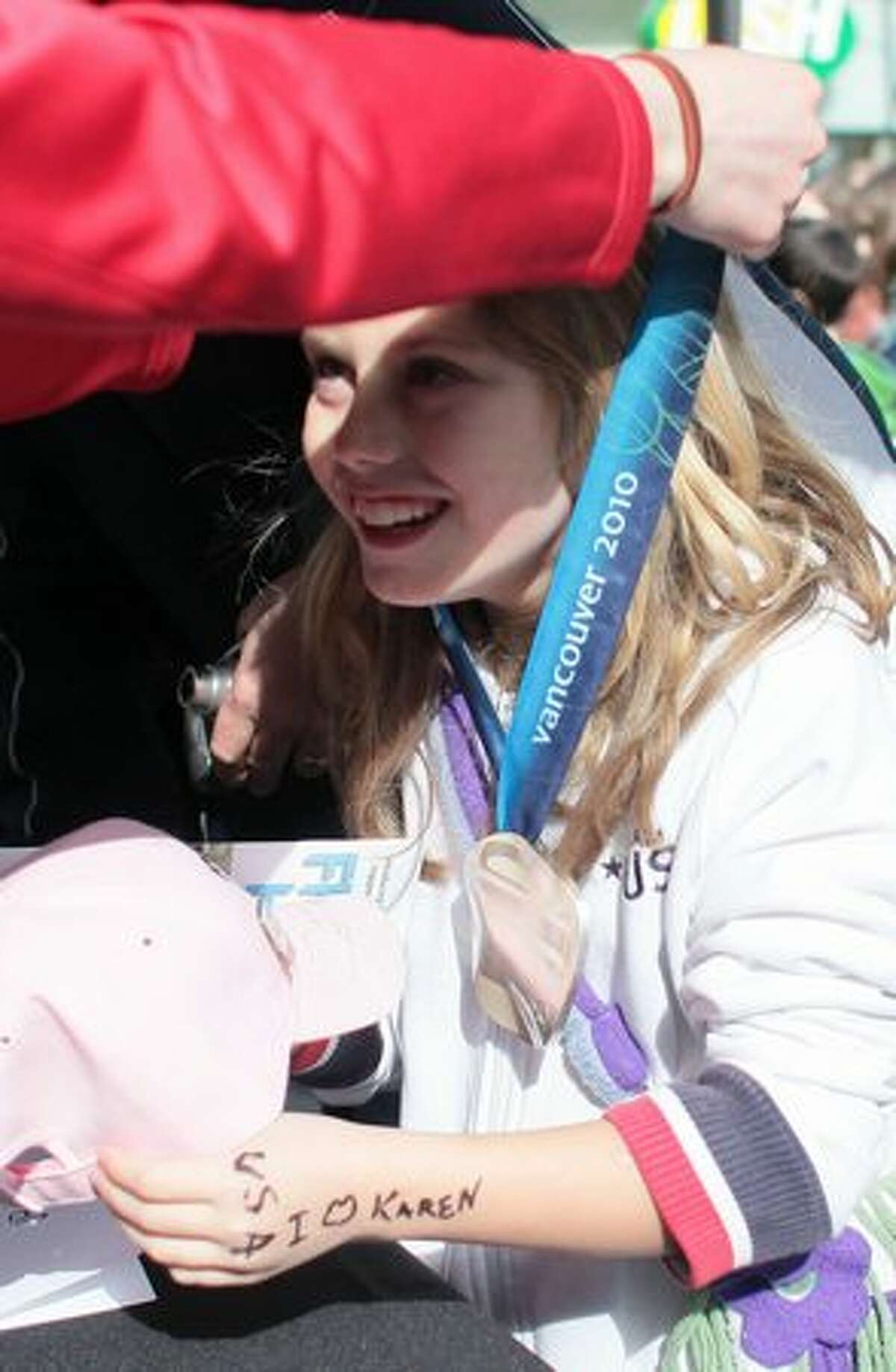Emily Kline, 9, a hockey player from Tacoma gets to try on Karen Thatcher's silver Olympic medal as local Olympians are welcomed home after competing in the Vancouver Olympics.