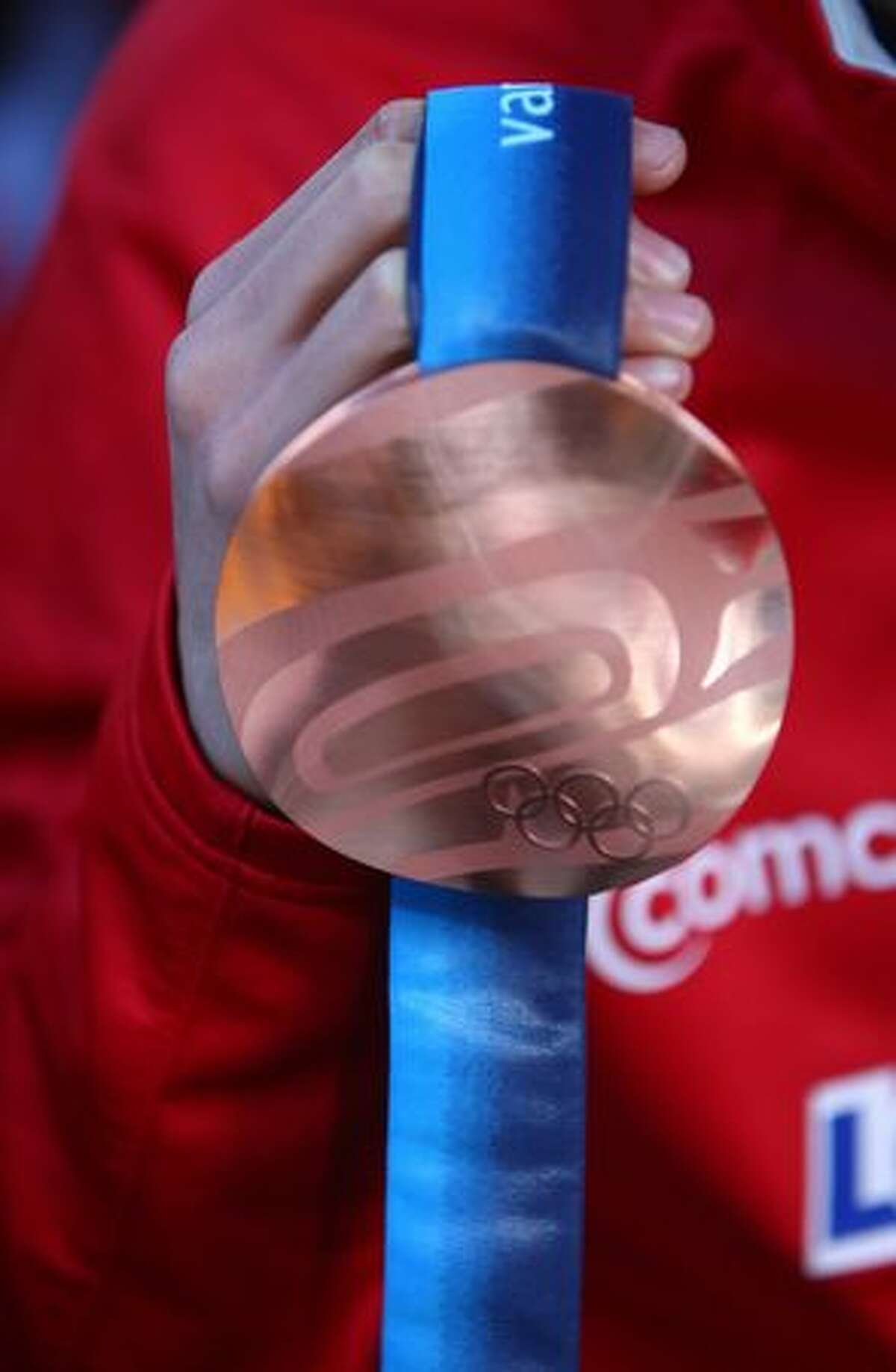 Olympic speedskater J.R. Celski shows his bronze medal during an event honoring local Olympians.