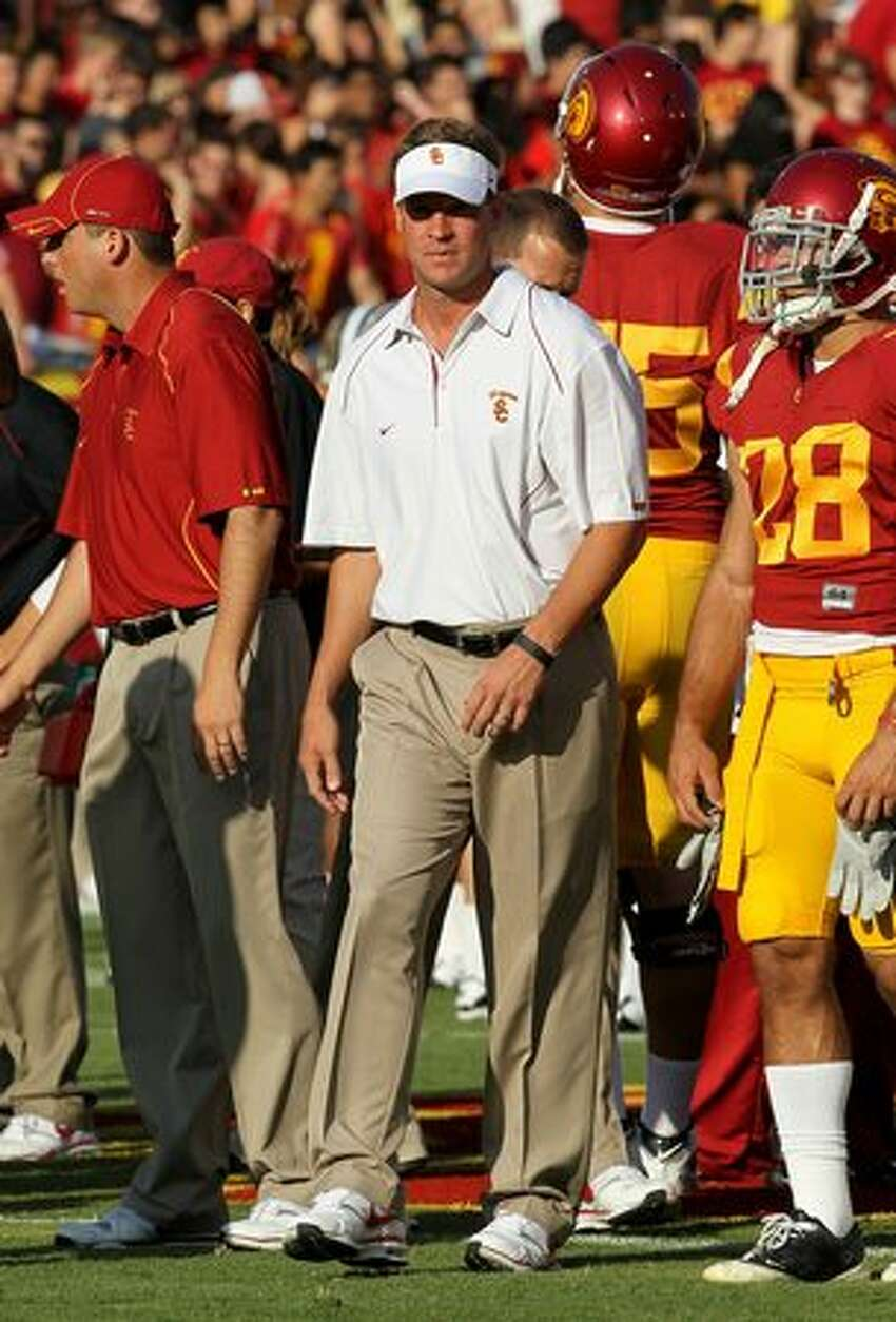 Head coach Lane Kiffin of the USC Trojans watches pregame warmups before the game with the Washington Huskies at the Los Angeles Memorial Coliseum on October 2, 2010 in Los Angeles, California.