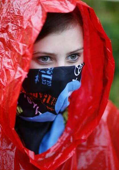 Demi Edwards, 16, tries to keep dry during day three of Bumbershoot, Seattle's annual music festival