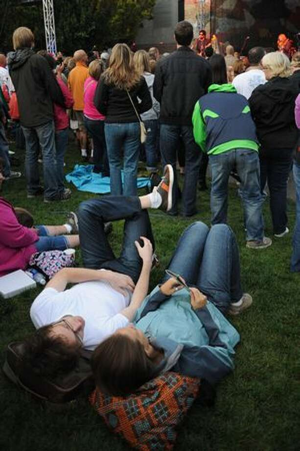 Bryn Johnson, left, and Erin Nacey, right, lie on the grass to listen to Bob Schneider's performance. Photo: Elliot Suhr, Seattlepi.com