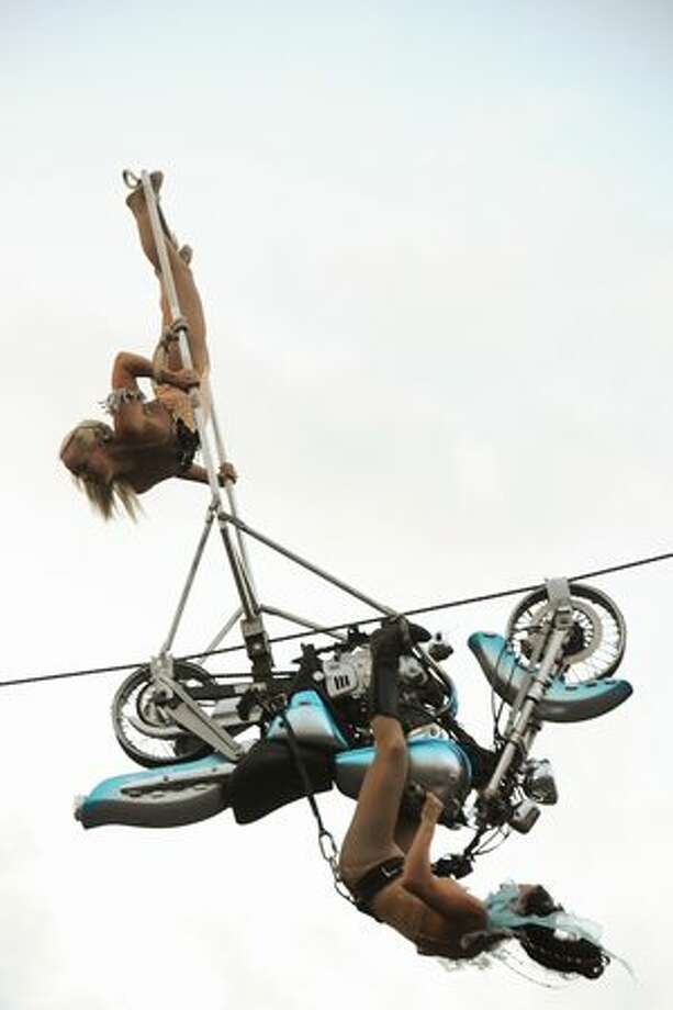 Performers from Circus Una seem to defy gravity as they ride a motorcycle upside down. Photo: Elliot Suhr, Seattlepi.com