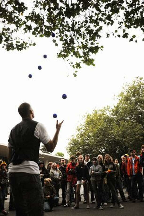 A street performer entertains a crowd by juggling seven balls. Photo: Elliot Suhr, Seattlepi.com