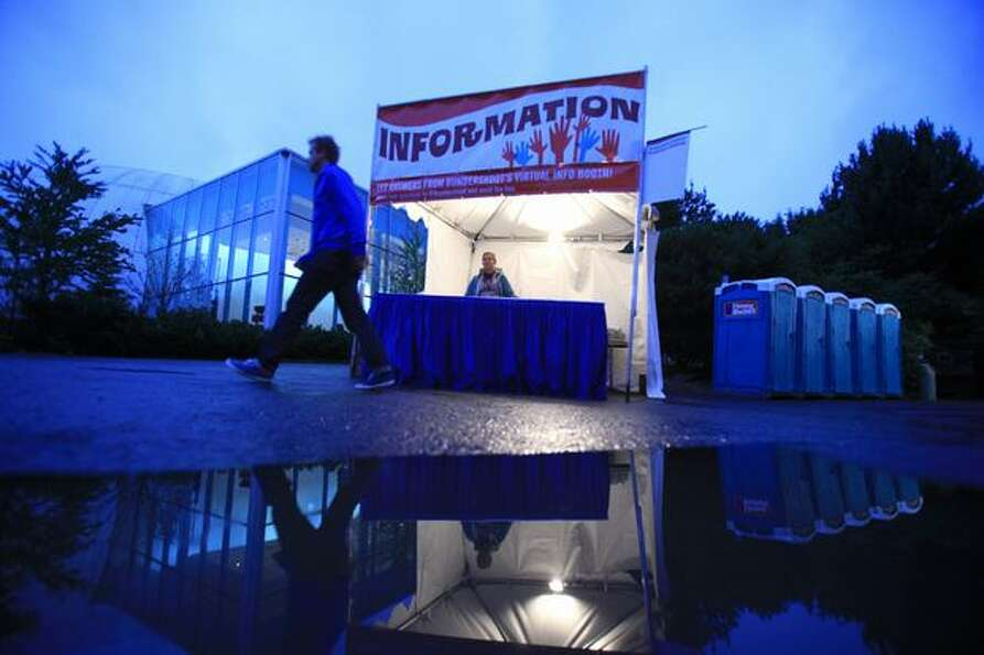 A person walks past an information kiosk after a steady rain during day three of Bumbershoot, Seattl