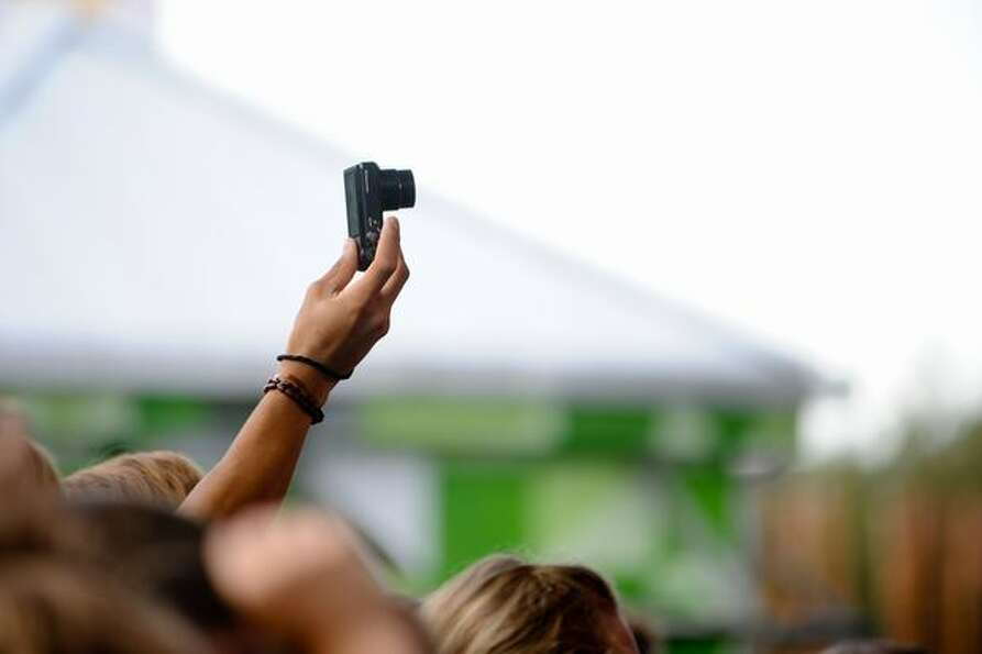 A fan sticks his camera above the crowd to take a photo of the Motion City Soundtrack.