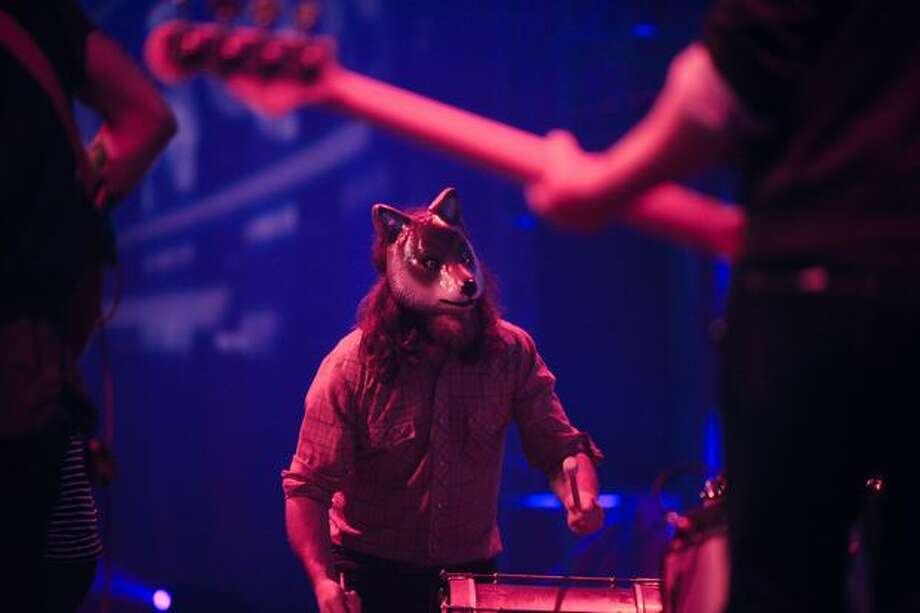 Band members wear wolf masks during a performance by Fences. Photo: Elliot Suhr, Seattlepi.com