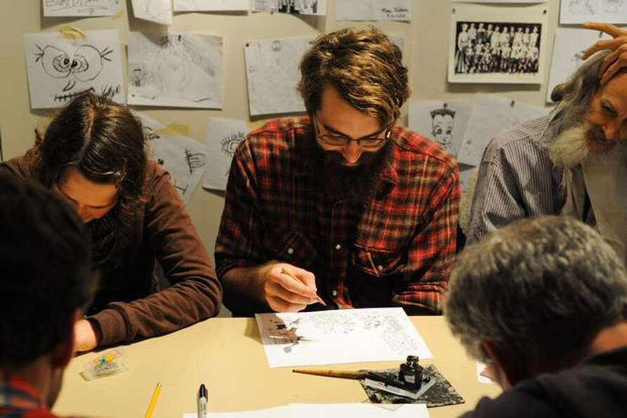 Artists gather together at a table to draw comics.
