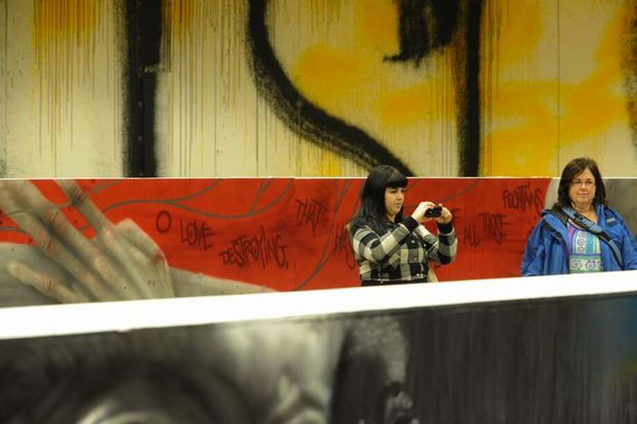 A girl takes a photo of the artwork at the Seattle Street Biennale 2010 in the Rainier Room. Photo: Elliot Suhr, Seattlepi.com