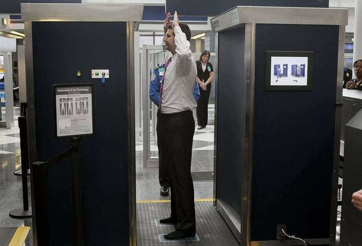 A Transportation Security Administration volunteer demonstrates a full-body scanner at Chicago O'Hare International Airport.