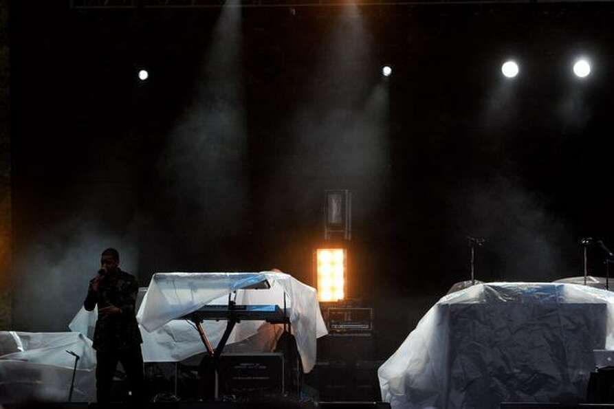 Instruments behind Cole are covered in plastic sheets to protect them from the rain.