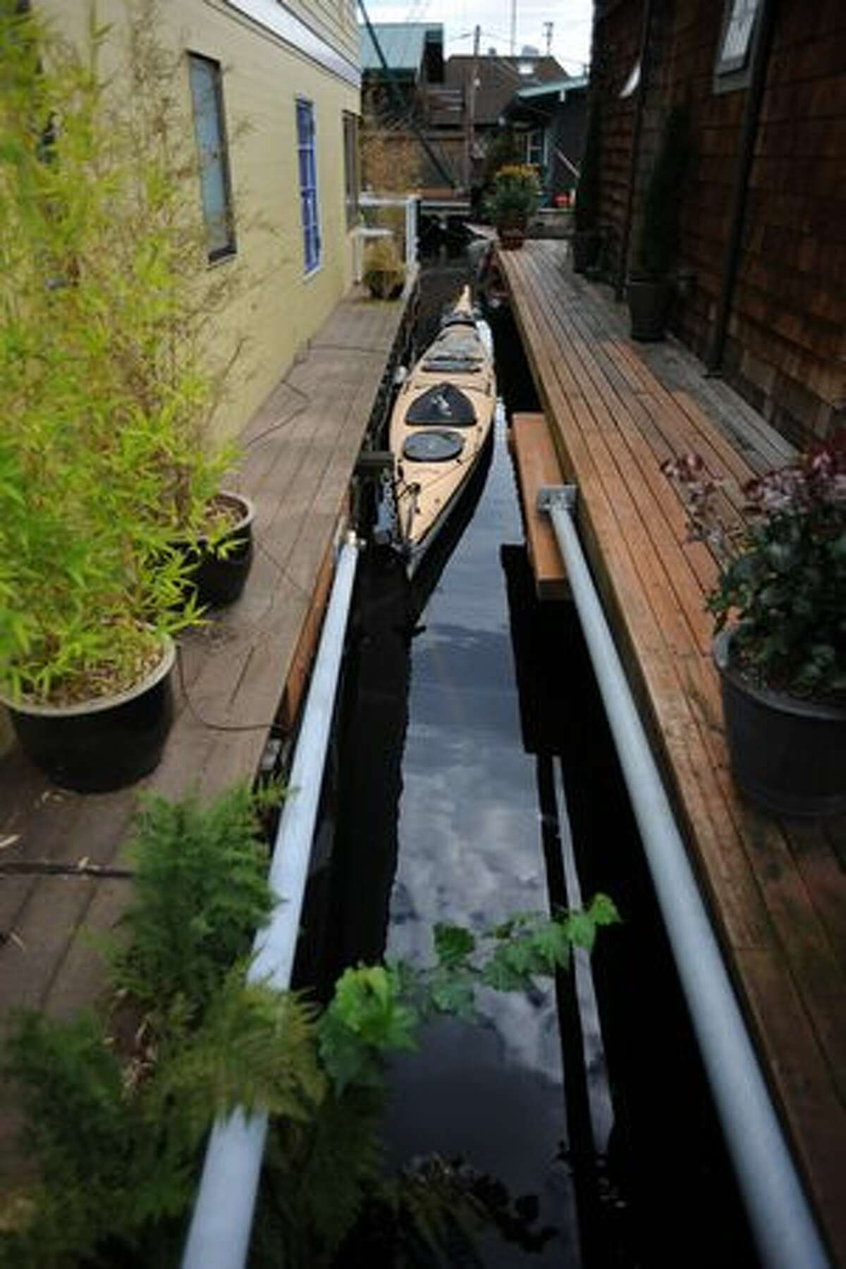 A kayak is tied down in the space between two houseboats at the 2010 Floating Homes Tour in Seattle.