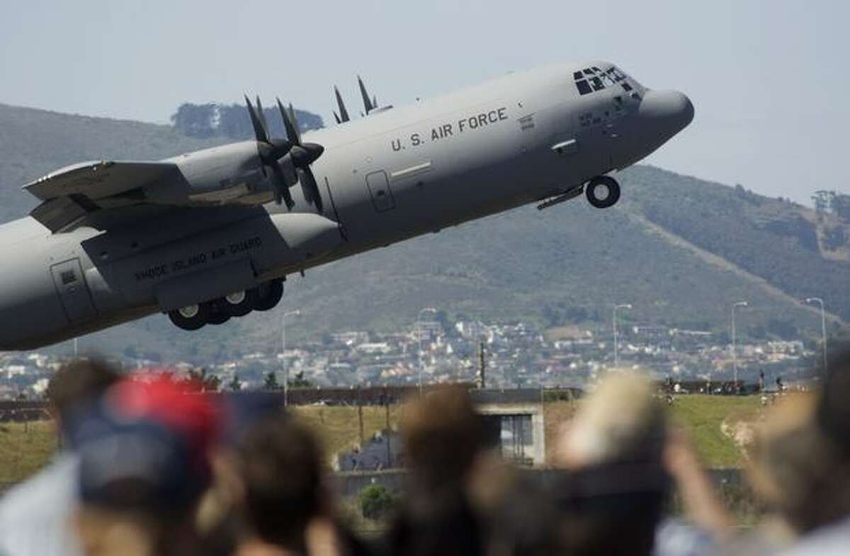 Members of the public watch as a U.S. Air Force Lockheed C130J takes off, during the Africa Aeronautics and Defence Airshow, at Ysterplaat Airforce Base in Cape Town, South Africa.