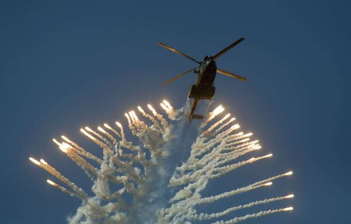 A South African Air Force Oryx helicopter fires flares during the Africa Aeronautics and Defence Airshow, at Ysterplaat Airforce Base in Cape Town, South Africa.