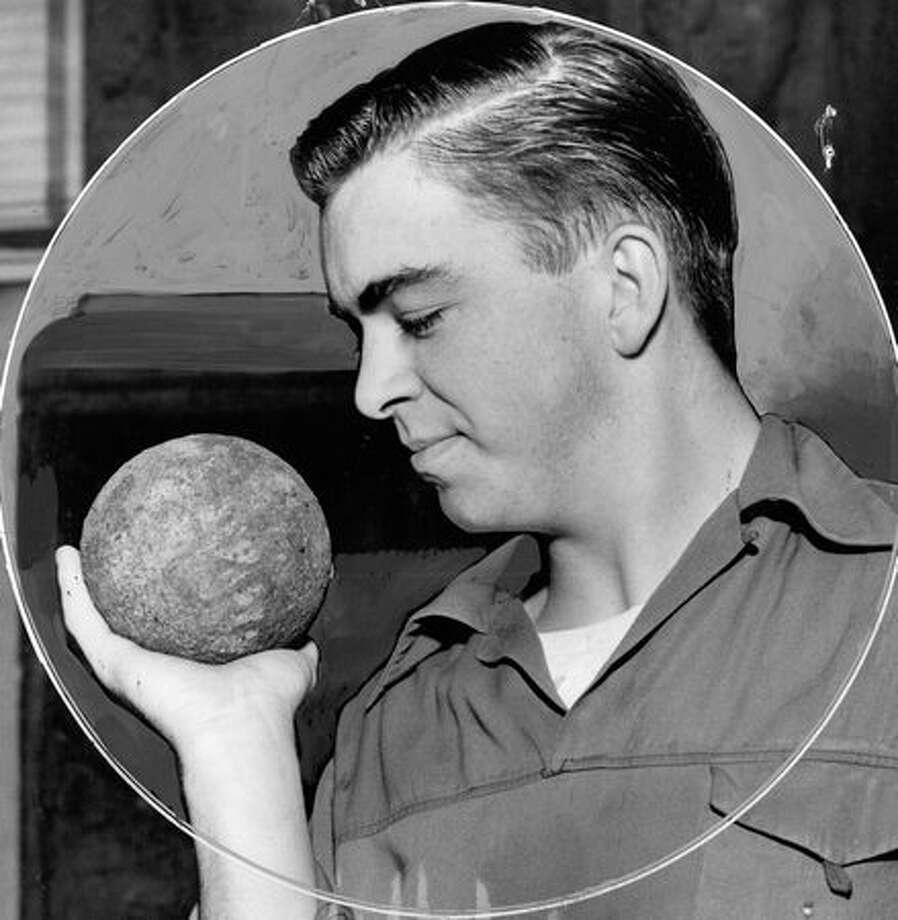 Jim Knisley holds a rusty iron cannon ball uncovered during an excavation for the Alaskan Way Viaduct, 1951. It is believed to have been fired in practice by a U.S. Navy vessel. Photo: P-I File