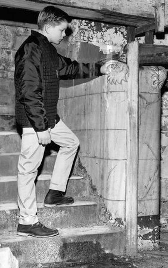 The January 1965 photo caption read: Wes Wilkins, a 13-year old Tacoma boy, examines a cast pineapple decoration on a concrete balustrade beside granite stairs that are far below 1st Avenue S. Wes went with his father, who accompanied the Seattle Junior Chamber of Commerce volunteers on a day-long tour of the Seattle underground in search of historic relics. Photo: P-I File
