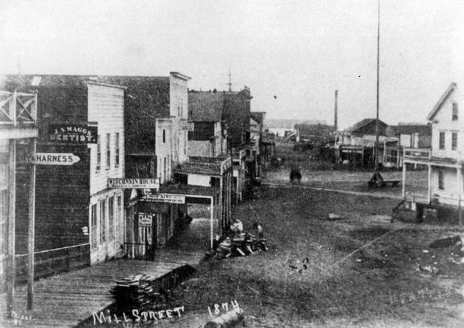 Information on the back of this photo indicates it shows Milll Street, now Yesler Way, with Henry Yesler's Mill in the background, 1874. Photo: P-I File