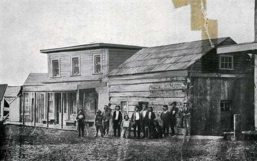 The earliest known photos of Seattle date to the 1850s and show the young city taking shape around Henry Yesler's Mill. This picture, dated 1866, shows the mill's cook house, built in 1853. Note how the neighboring adjacent building, constructed in the intervening years, exhibit more refined craftsmanship than the cook house's roughly-sawed timbers.