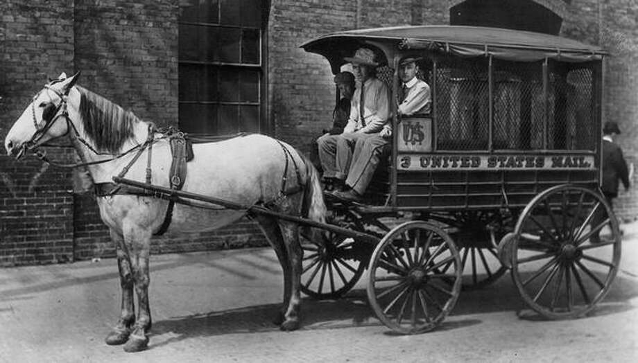 The original P-I photo caption read: The original parcel post delivery wagon, put into service when the system began in 1913. On the wagon are Driver George Lawler and Carriers Jack Daly and H.S. Parker. Photo: P-I File