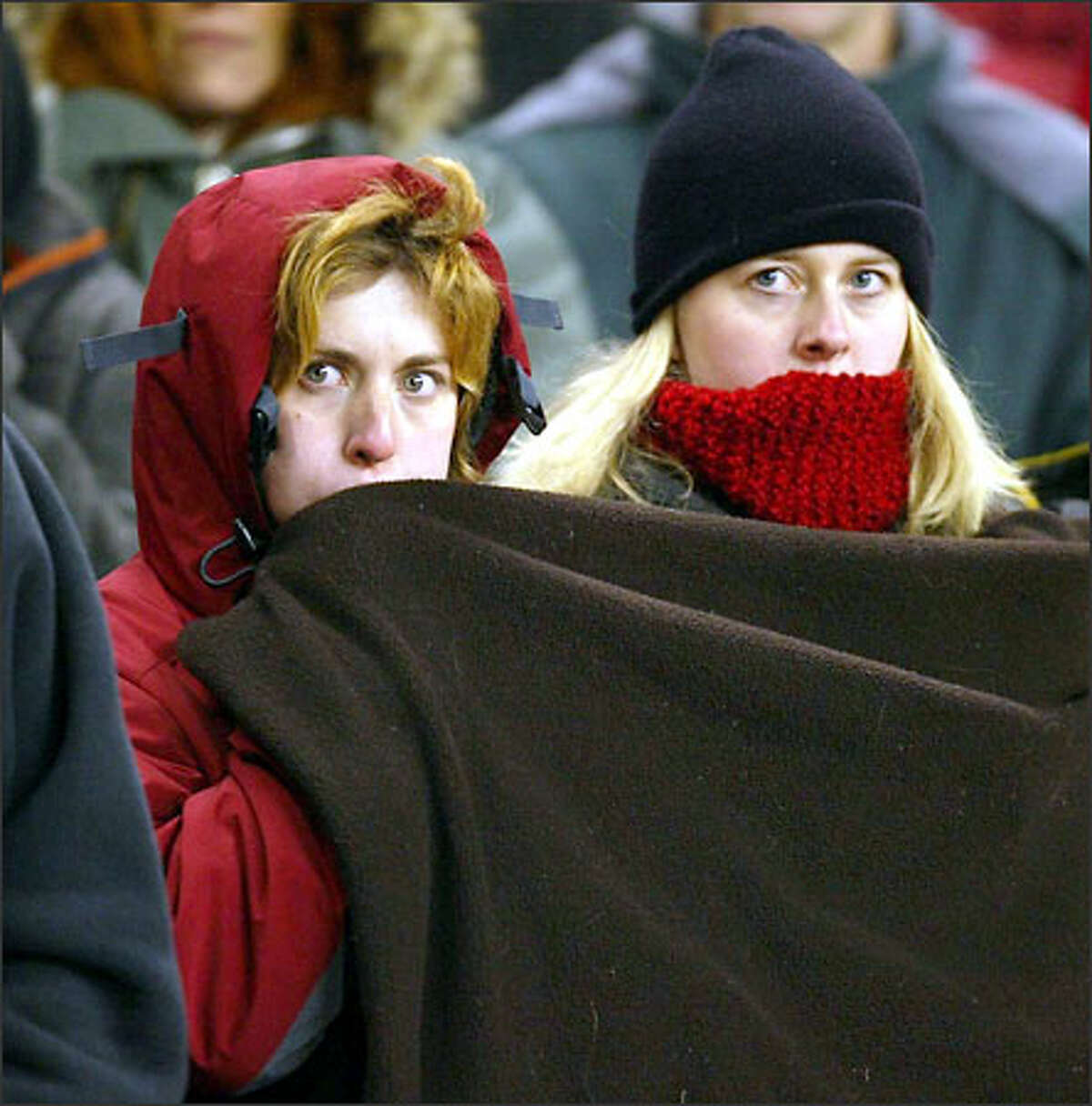 A pair of Cougar fans watch game.