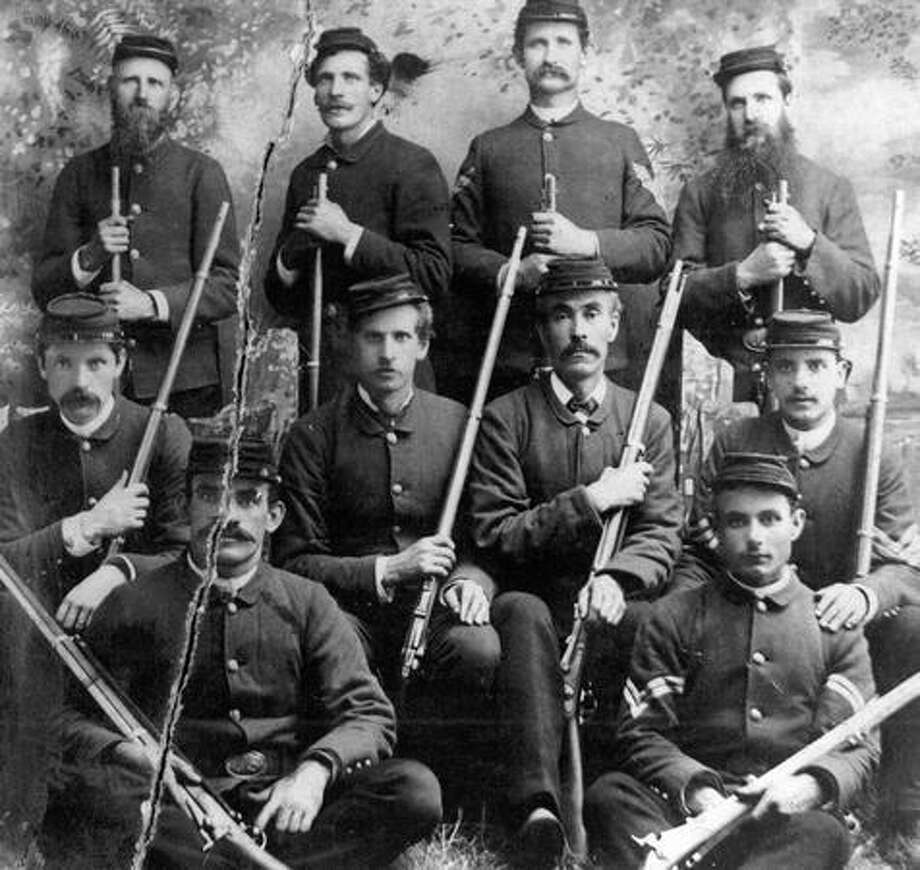 The P-I photo caption read: This is the first rifle team organized in Washington. They went undefeated. Back row, left to right, is J. Edwards; L. Anderson, J. Brennan and A. Anderson; (second row) H. Argens, E. Anderson, C. Cowen, [name illegible]; (front) Ed Clark and R. Hummel. Photo: P-I File