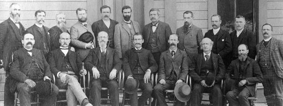 The original P-I photo caption read: This is the last Grand Jury of King County to sit while Washington was still a territory. From left to right, standing: H. Wells, G.W. Poor, S.B. Elder, M. Clericus, J.C. Helms, W.D. Fenton (deputy district attorney), W.H. White (U.S. attorney), H. Bode, D. Benton, I. Monahan and A. Gaston. Seated: W.H. Johnson, S.F. Compton, R.C. Crawford, A.M. Gilman, W. H. Gleason, D.H. Hawley, and J.W. Borst. Photo: P-I File
