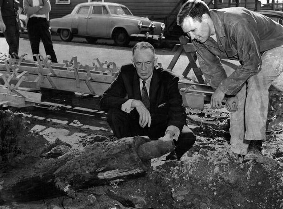 The October 1963 photo caption read: A section of the city's first water system -- a length of hollowed fir log -- is examined by Victor Denny, left, president of the Seattle Historical Society, and Jack Feeker, president of the Pioneer Businessmen's Association. The ancient water line was unearthed at Sixth Avenue and James Street by crews working on the Seattle Freeway. Photo: P-I File