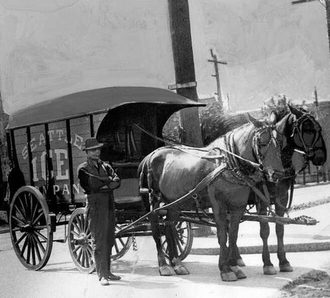 Hans Romstead, ice delivery man, stands beside his wagon and team at Sixth Avenue and Pike Street in