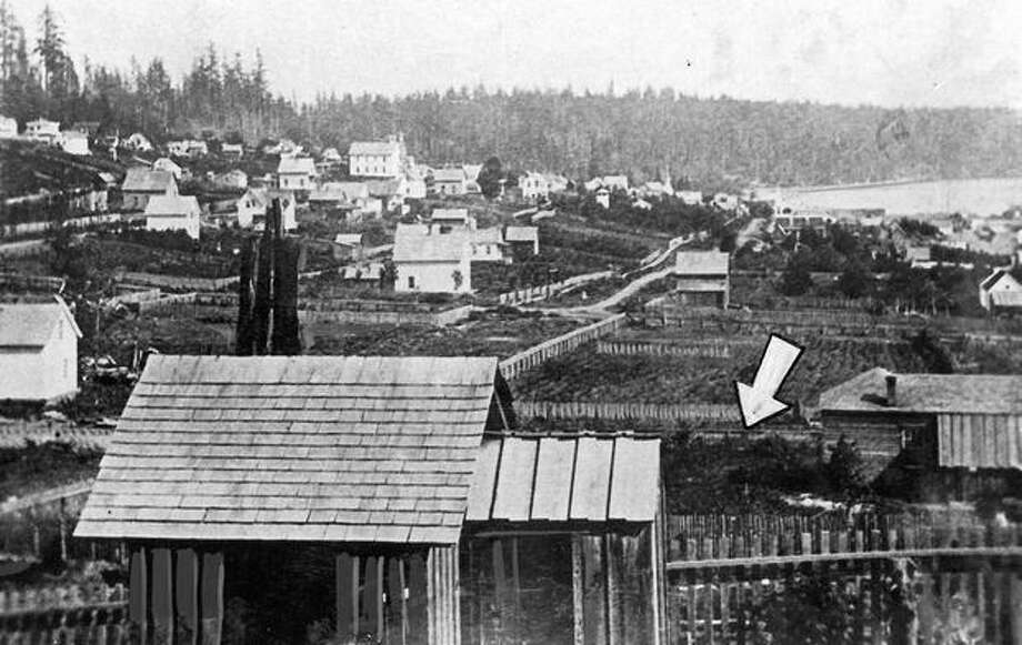 The P-I photo caption read: The arrow in this photograph points to the Seattle Coal and Iron Co. railroad tracks over which coal from Newcastle was carried from Lake Union to bunkers on the Seattle waterfront at the foot of Pike Street, 1871. Photo: P-I File