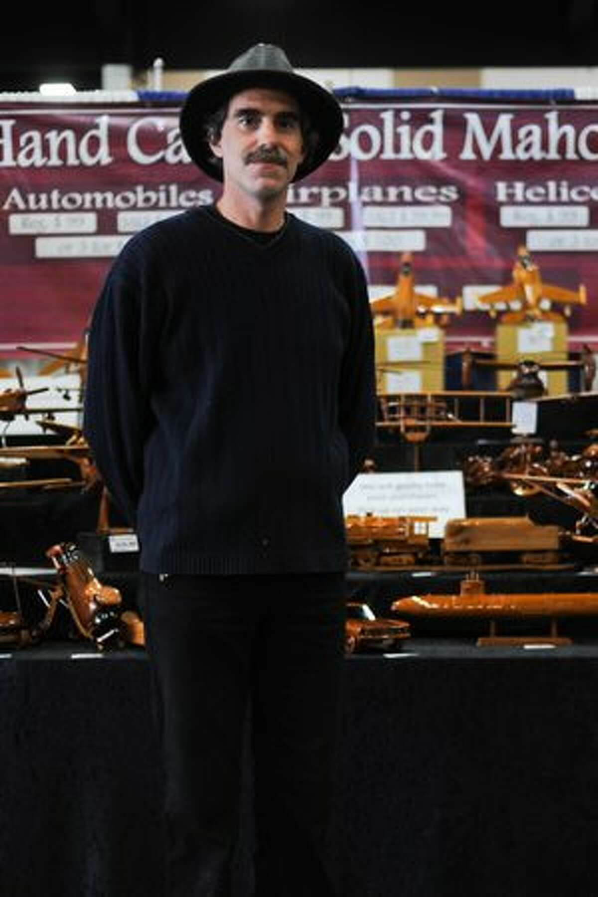 Mike Rhodes stands in front of his booth selling hand-carved mahogany models. He says the carvings originate from a village in Saigon, Vietnam and have been produced for over 27 years.