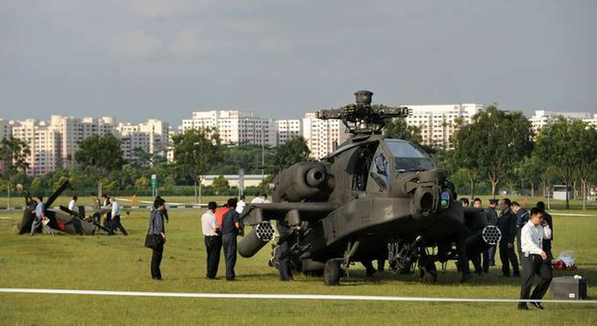 A Republic of Singapore Air Force Apache AH-64 helicopter sits on the field with its tail detached after it crashed in Singapore.