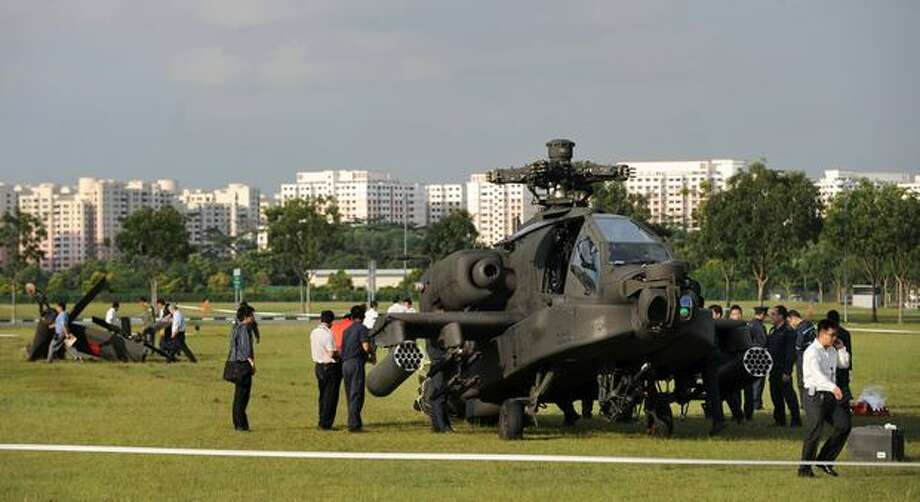 A Republic of Singapore Air Force Apache AH-64 helicopter sits on the field with its tail detached after it crashed in Singapore. Photo: Getty Images