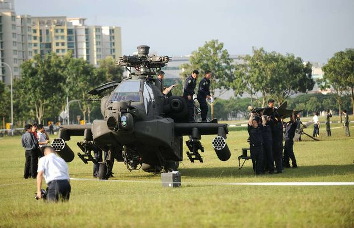 A Republic of Singapore Air Force Apache AH-64 helicopter sits on a field as its tail is carried by air force engineers after it crashed in Singapore.