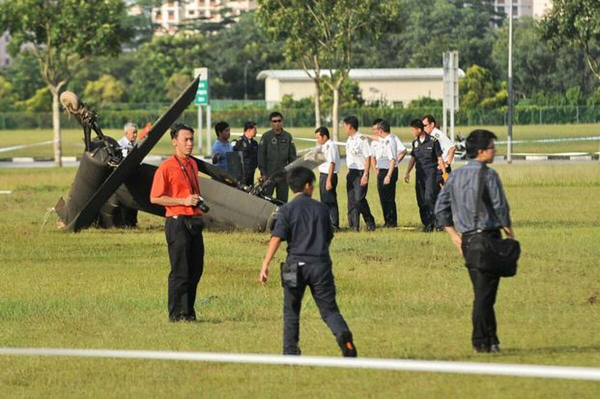 The tail of a Republic of Singapore Air Force Apache AH-64 helicopter sits on a field after the helicopter crashed in Singapore.