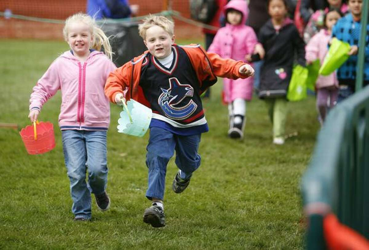 Jasmine Paulk, 6, and her brother Kevin Paulk, 6, sprint to to the start line during the annual Bunny Bounce Easter egg hunt at Woodland Park Zoo on Saturday April 3, 2010 in Seattle.