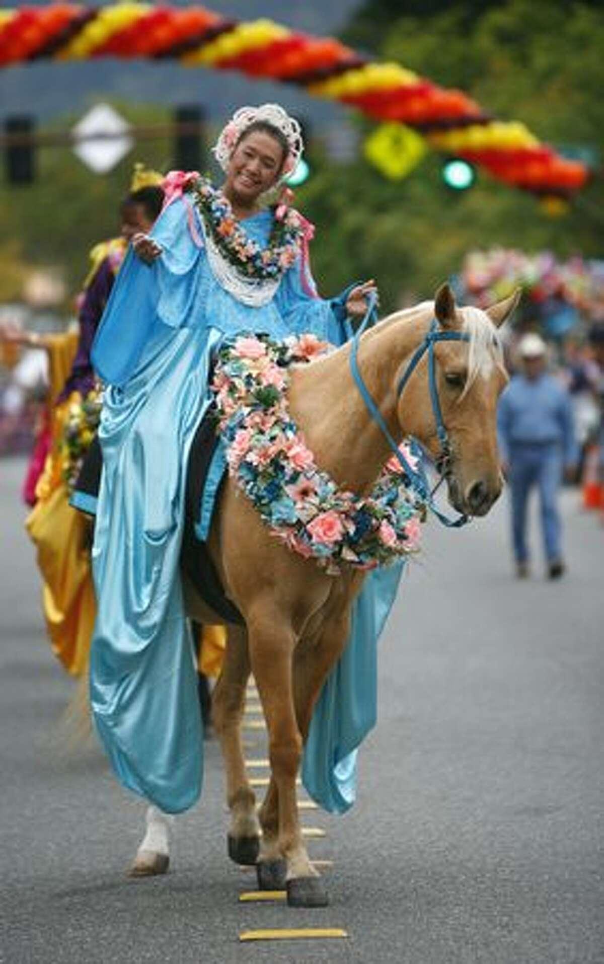 Kau Lio Pa'u Riders, a Hawaiian riding group, make their way along Front Street.