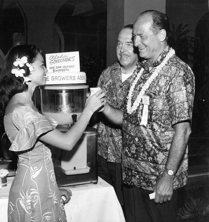 The July 1961 photo caption read: Washington State Governor Albert Rosellini, right, receives a glass of pineapple juice from pretty Mary Ann Summers at the 52nd Governors' Conference in Honolulu. Photo: P-I File