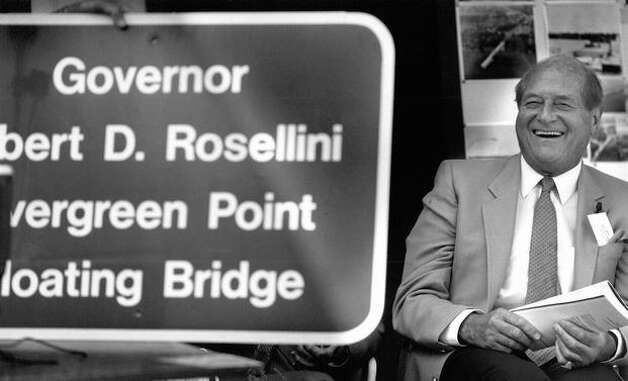 The man the 520 bridge is now named after, former Gov. Albert D. Rosellini, relaxes beside a new sign during ceremonies yesterday marking the 25th anniversary of Lake Washington's Evergreen Point Floating Bridge. Photo by Mike Bainter, Aug. 28, 1988. Photo: P-I File