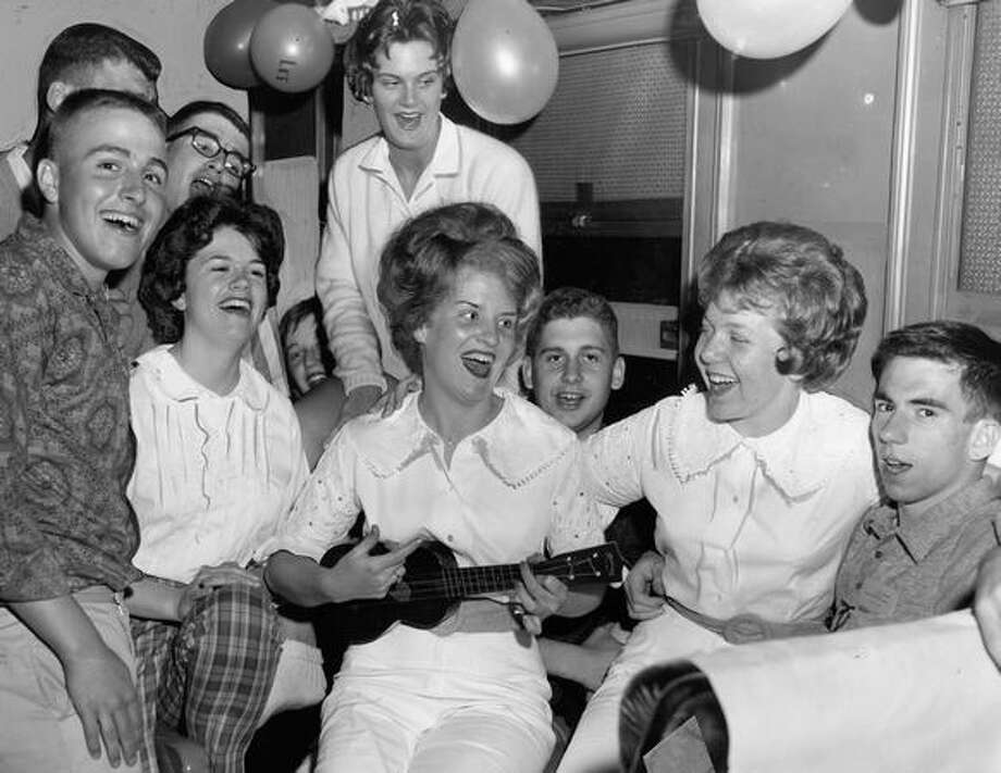 The original photo caption read: Queen Anne high School graduates, changed from party clothes into casual outfits, sing to the music of Lynn Pearce's ukelele enroute to Tacoma for breakfast on a Northern Pacific special train. Photo by Vallentyne. June 10, 1961. Photo: P-I File