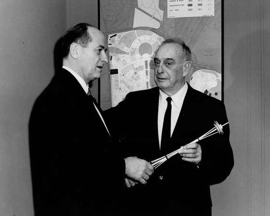 The March 1962 photo caption read: Gov. Albert D. Rosellini of the State of Washington presents a model of the Space Needle, symbol of the Seattle World's Fair, to Robert Moses, president of the New York 1964-1965 World's Fair, as he visited the site of the New York Fair today. Photo: P-I File