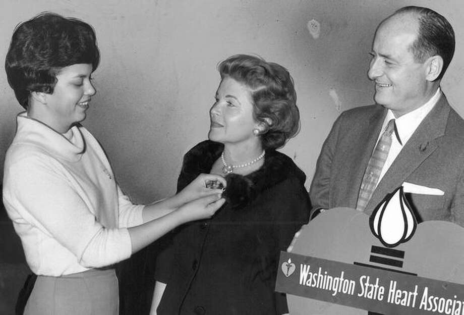 The Feb. 1961 photo caption read: Penny Allen, Washington State Heart Association mascot, pins emblem on Mrs. Albert D. Rosellini designating her as the No. 1 Heart Fund campaign volunteer. Photo: P-I File