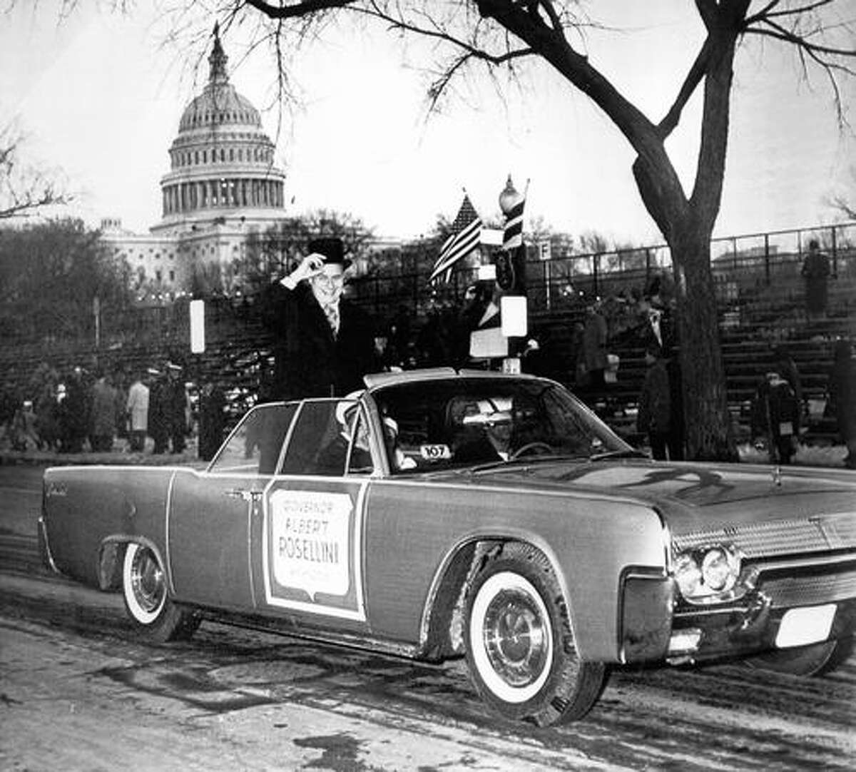 The January 1961 photo caption read: Smiling Gov. Albert Rosellini puts his hand to his heart as he acknowledges cheers from spectators along Constitution Avenue, part of inaugural parade route today.