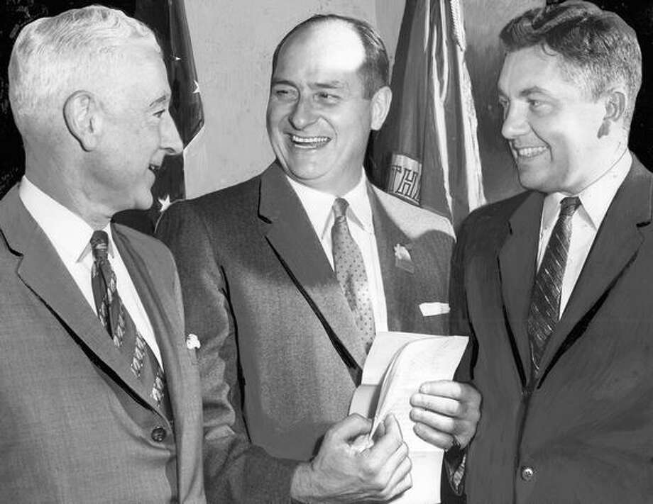 The March 1960 photo caption read: Getting together before dinner at which Gov. Albert D. Rosellini was honored last night were the Governor (center); Stanly Donogh (left), chairman, Statewide Labor and Industry Committee, and H. McKinley Conway Jr., editor-publisher of Industrial Development Magazine. Photo: P-I File