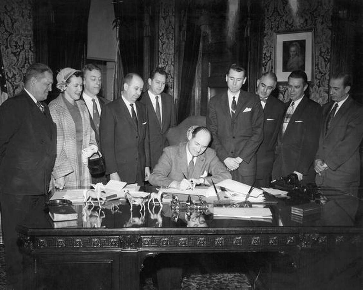 The April 1957 caption read: With a delegation from Bellevue looking over his shoulder, Gov. Rosellini signs a bill authorizing a second bridge across Lake Washington.