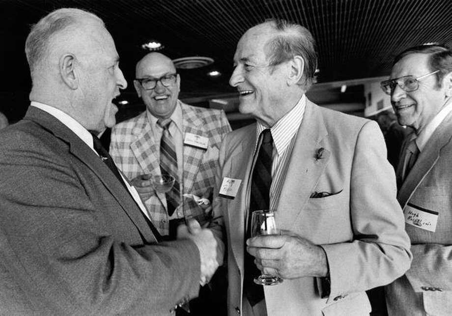 Bill Howard shakes hands with former Gov. Al Rosellini as John Sterbick looks on. Hugh Rosellini is on the right. May 13, 1983. Photo: P-I File