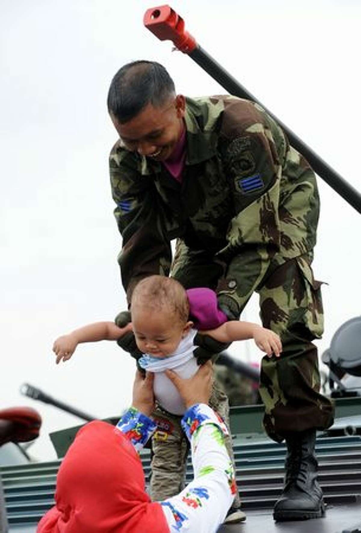 An Indonesian soldier hands over a toddler to his mother after having a picture taken on a tank during the 65th Indonesian military anniversary in Jakarta.