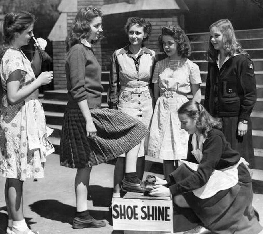 The May 1946 photo caption read: Beverly Eckert, chairman of Lincoln High School health week committee, gets her shoes shined by Anita Roe, and her sweater brushed by Marie Wiley. Others waiting for good grooming services are (left to right) Marilyn Cook, Joan Keller and Billie Manring. Photo: P-I File