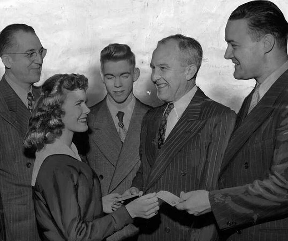 The February 1948 photo caption read: Two of Lincoln High School's better-known graduates, Mayor William F. Devin and Police Chief George D. Eastman, both at right, were presented Lincoln alumni cards yesterday by one of the school's prettier undergraduates, Themla DeLong, as a reminder of the Lincoln reunion Thursday. Looking on are Principal Earl Pfaff and Dick Barrett, student body president. Photo: P-I File